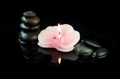 Vela ardente na forma da flor e dos seixos da orquídea no fundo preto Imagem de Stock Royalty Free