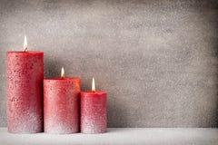 Vela ardente vermelha em um fundo da neve artigos do interior da imagem 3D Foto de Stock Royalty Free