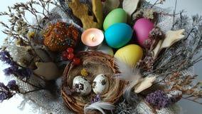 Vela ardiendo de la luz del té en una cesta de Pascua