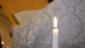 Vela ardiente blanca en el chirch ortodoxo en las manos de un fondo del rezo de un sacerdote