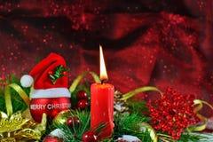 Vela ardiente con la chuchería roja con el sombrero de Papá Noel y las decoraciones de la Navidad Fotos de archivo libres de regalías