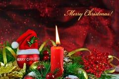 Vela ardiente con la chuchería roja con el sombrero de Papá Noel y las decoraciones de la Navidad Imagen de archivo libre de regalías