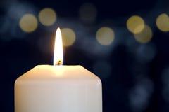 Vela ardiente con las luces de oro Foto de archivo libre de regalías