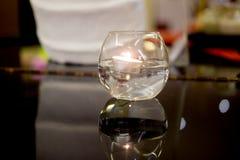 Vela ardiente de la cera de abejas en el cuenco cristalino Imagen de archivo libre de regalías