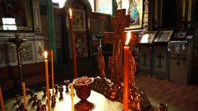 Vela ardiente de la iglesia cerca de la cruz de oro Primer video almacen de metraje de vídeo