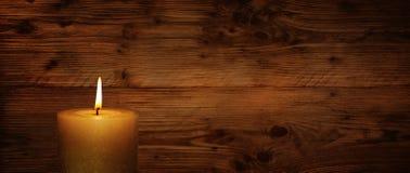 Vela ardiente delante de la pared de madera rústica Imagen de archivo libre de regalías