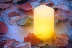 Vela ardiente en niebla en la tabla de madera con las hojas de otoño Foto de archivo libre de regalías