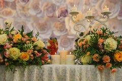 Vela ardiente que se coloca en la tabla en el ambiente de flores Imagenes de archivo