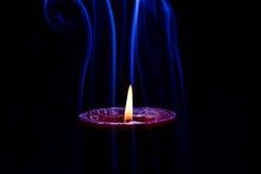 Vela ardiente roja con humo coloreado azul imagen de archivo