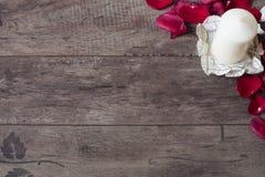 Vela aromática blanca de la vainilla y pétalos color de rosa rojos Fondo de madera Concepto de Aromatherapy fondo romántico marco Fotos de archivo