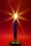Vela azul no suporte de bronze no vermelho. fotografia de stock royalty free