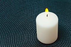 Vela blanca ardiente en un fondo azul Fotos de archivo libres de regalías