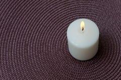 Vela blanca ardiente en un fondo púrpura Fotografía de archivo