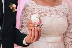 Vela blanca con una decoración de flores en las manos de los recienes casados El concepto del hogar de la familia imagen de archivo libre de regalías