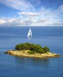 Vela blanca sola cerca de la isla Foto de archivo libre de regalías
