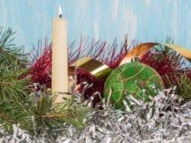 Vela blanca, una bola verde del árbol de navidad, una malla del árbol de navidad Nuevo year& x27; fondo de s Imagen de archivo libre de regalías
