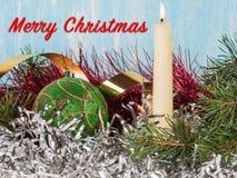 Vela blanca, una bola verde del árbol de navidad, una malla del árbol de navidad Nuevo year& x27; fondo de s Fotografía de archivo libre de regalías