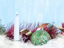 Vela blanca, una bola verde del árbol de navidad, una malla del árbol de navidad Nuevo year& x27; fondo de s Fotografía de archivo