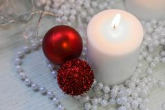 Vela branca, bolas vermelhas do Natal, grânulos perly brancos Foto de Stock Royalty Free