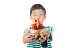 Vela browing do rapaz pequeno no bolo para seu aniversário fotos de stock