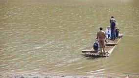 Vela caucasiano dos turistas na jangada Guy Throws Rope através do lago video estoque