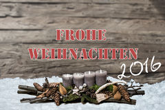 A vela cinzenta ardente da decoração 2016 do Feliz Natal borrou o alemão da mensagem de texto da neve do fundo Fotos de Stock