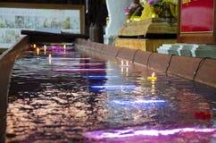 A vela colorida rezando ritual que flutua na água para reza a imagem de reclinação da Buda em Wat Phra Non Chakkrasi Worawihan em foto de stock royalty free