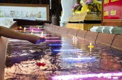 A vela colorida rezando ritual que flutua na água para reza a imagem de reclinação da Buda em Wat Phra Non Chakkrasi Worawihan em fotografia de stock