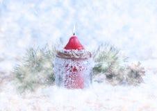 Vela, cones e ramos spruce em um fundo de madeira coberto de neve Imagens de Stock