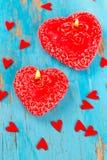Vela, corações e fitas vermelhos em uma superfície de madeira azul Imagem de Stock Royalty Free