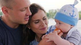 A vela da família, bebê que come seu primeiro frutifica em mamãs das mãos, família com a criança no fim de semana, pais e criança filme