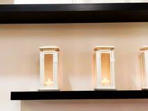 A vela da lâmpada em uma caixa transparente pendura na parede na sala como a decoração da decoração e da sala fotos de stock