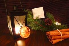 A vela da lanterna elétrica com Livro Branco, a laranja, a canela e o pinho ramificam Imagem de Stock Royalty Free