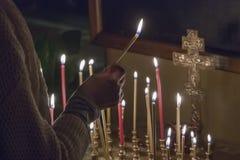 Vela da oração da iluminação da mulher foto de stock