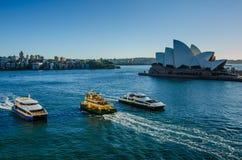 Vela das balsas de passageiro após Sidney Opera House, Foto de Stock