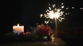 Vela de la Navidad con el fuego de Bengala en un fondo negro en la c?mara lenta estupenda almacen de metraje de vídeo