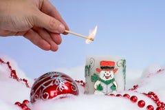 Vela de la Navidad de la iluminación de la persona con las decoraciones alrededor de ella Imagen de archivo libre de regalías