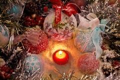 Vela de la Navidad en la nieve rodeada por los juguetes y las bolas de la Navidad Imagenes de archivo