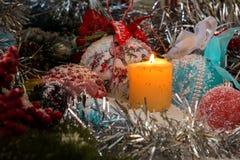 Vela de la Navidad en la nieve rodeada por los juguetes y las bolas de la Navidad Imágenes de archivo libres de regalías