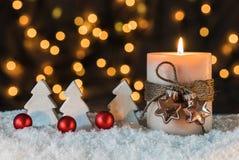 Vela de la Navidad y decoración blanca de los árboles en la noche Foto de archivo
