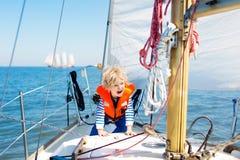 Vela de los niños en el yate en el mar Navegación del niño en el barco fotos de archivo