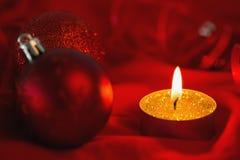 Vela de oro de la luz del té con las decoraciones de la Navidad Foto de archivo
