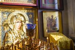 Vela de queimadura na igreja ortodoxa no fundo do ícone da mãe do deus imagens de stock