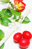 Vela de Rosa, de Páscoa e ovos vermelhos Fotografia de Stock Royalty Free