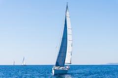 Vela de um barco de navigação iate da navigação no mastro da água Fotografia de Stock Royalty Free