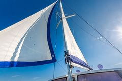 Vela de un barco de navegación contra el cielo con los rayos del sol imagen de archivo