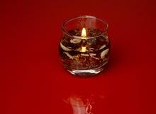 Vela de vidro decorativa no vermelho isolado Fotos de Stock