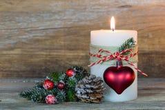 Vela del advenimiento con el ornamento del corazón y la rama de árbol de abeto fotos de archivo