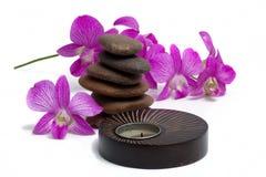 Vela del balneario y piedras equilibradas con la orquídea Fotos de archivo libres de regalías