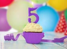 Vela del cumpleaños con el número 5 en la magdalena Fotos de archivo libres de regalías